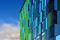 Glass colorful facade with cloudy sky Royalty Free Stock Images
