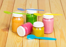 Glass colorful jars of baby food on  background  light wood. Stock Photos