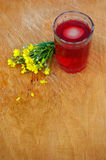Glass of compote on wooden table. Glass of compote and flowers on scratched wooden table Royalty Free Stock Photo