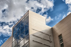 Glass and concrete. The sky and clouds are reflected in glasses of the building Stock Images
