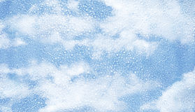 Glass with condensation of water droplets and blue sky Royalty Free Stock Photos