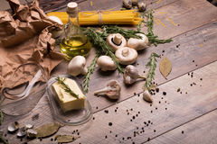 A glass container with butter next to mushrooms, pasta and oil bottle. Raw ingredients on a wooden table background. A view from above on a piece of butter in a Stock Images