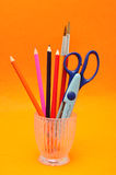 A glass container with scissors and pencils Royalty Free Stock Images