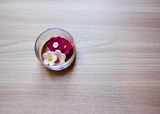 Glass containers with Garden felt flowers over wooden background stock image