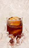 Glass of cool cola on ice background Royalty Free Stock Image