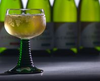 Glass of cool white wine. Served in a typical glass. In background, four bottles of wine royalty free stock image