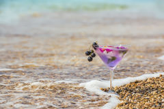 A glass with a cooling drink in the foam of the sea surf on the beach among the pebbles. Stock Image