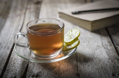 Glass of cooling lemon tea on wooden table with book and pencil Stock Image
