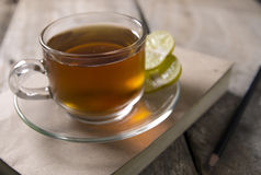 Glass of cooling tea on wooden table with book and pencil Stock Photography