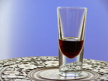 Glass cordial. A glass of averna, an italien cordial, with a blue background on a beautiful little table with ornaments stock photo