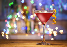 Glass of cosmopolitan cocktail. On a bar lights background stock photography