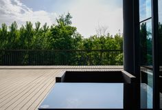 Glass-covered table and armchair on planked terrace in sunny sum Royalty Free Stock Photo
