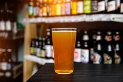 Glass of craft beer at the bar. Assortment of bottles on a blurred background stock photos