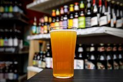 Glass of craft beer at the bar. Assortment of bottles on a blurred background. Glass of craft beer at the bar. Assortment of bottles on a blurred background royalty free stock photos