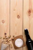 Glass of craft beer, bottle and pistachio nuts on wood background. Top view, copy space. Royalty Free Stock Image