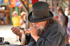 Glass Crafting. A tophat wearing craftsman demonstrates his process of creating a glass sculpture using a dragon blow torch Stock Images