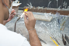 Glass craftsman making a glass sculpture. Stock Photo
