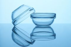 Glass crockery on reflective surface. Two transparent bowls royalty free stock images