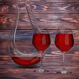 Glass Crystal Decanter with Red Wine and Two Wine Glasses. 3d Re. Glass Crystal Decanter with Red Wine and Two Wine Glasses on a wooden table. 3d Rendering Royalty Free Stock Image