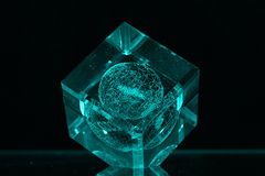 Glass cube on dark backgroud. Glass cube with globe inside Stock Photo