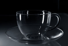 Glass cup. On a black background with highlights Royalty Free Stock Image