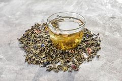 Glass cup of aromatic green tea and dry leaves on grey background royalty free stock photo