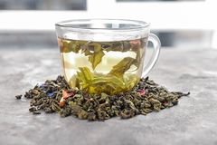 Glass cup of aromatic green tea and dry leaves on table stock photo