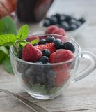Glass cup with berries, blueberries, raspberries, strawberries, and mint. On the wooden table light stock photography