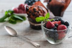 Glass cup with berries, blueberries, raspberries, strawberries, and mint. On the wooden table light stock image