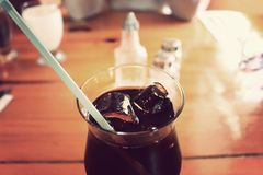 Glass Cup With Black Liquid and Green Straw on Brown Wooden Royalty Free Stock Image