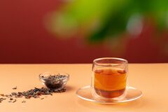 Glass cup of black tea on beige table