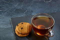 A glass cup of black tea with brownies on a dark greyish marble background. Breakfast background. A transparent glass cup of black tea with cookies on a dark Royalty Free Stock Photos