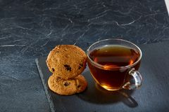 A glass cup of black tea with brownies on a dark greyish marble background. Breakfast background. A transparent glass cup of black tea with cookies on a dark Stock Image