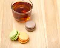 Glass cup of black tea and colorful macarons Royalty Free Stock Images