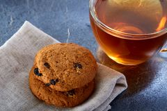 A glass cup of black tea with cookies on a dark greyish marble background. Breakfast background. A transparent glass cup of black tea with cookies on a dark Stock Image