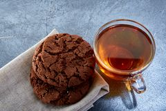 A glass cup of black tea with cookies on a dark greyish marble background. Breakfast background. A transparent glass cup of black tea with cookies on a dark Royalty Free Stock Image