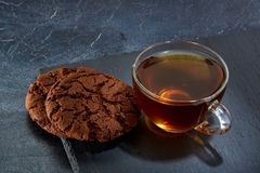 A glass cup of black tea with cookies on a dark greyish marble background. Breakfast background. A transparent glass cup of black tea with cookies on a dark Stock Photography