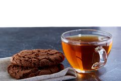 A glass cup of black tea with cookies on a dark greyish marble background. Breakfast background. A transparent glass cup of black tea with cookies on a dark Royalty Free Stock Photography