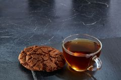 A glass cup of black tea with cookies on a dark greyish marble background. Breakfast background. A transparent glass cup of black tea with cookies on a dark Royalty Free Stock Photo