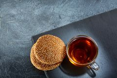 A glass cup of black tea with cookies on a dark greyish marble background. Breakfast background. A transparent glass cup of black tea with cookies on a dark Stock Photos
