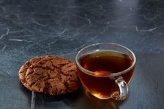 A glass cup of black tea with cookies on a dark greyish marble background, selective focus. Breakfast background. A transparent glass cup of black tea with Royalty Free Stock Photo