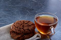 A glass cup of black tea with cookies on a dark greyish marble background, selective focus. Breakfast background. A transparent glass cup of black tea with Stock Photography
