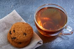 A glass cup of black tea with cookies on a dark greyish marble background, shallow depth of field. Breakfast background. A transparent glass cup of black tea Stock Photos