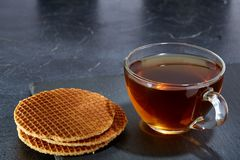 A glass cup of black tea with waffles on a dark greyish marble background. Breakfast background. A transparent glass cup of black tea with waffles on a dark Stock Photos