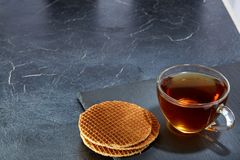 A glass cup of black tea with waffles on a dark greyish marble background. Breakfast background. A transparent glass cup of black tea with waffles on a dark Royalty Free Stock Image