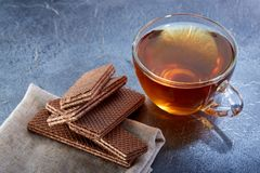 A glass cup of black tea with waffles on a dark greyish marble background, selective focus. Breakfast background. A transparent glass cup of black tea with tasty Stock Images