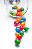 Glass cup with candies spilled out Royalty Free Stock Photo