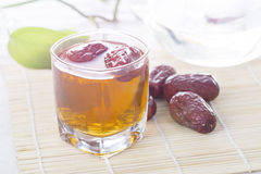 A glass cup of Chinese red date tea on the table. Royalty Free Stock Photo
