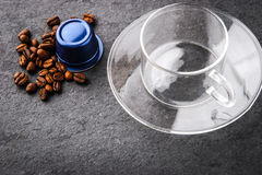 Glass cup with coffee capsule and coffee beans Stock Images