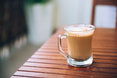Glass or cup of coffee with white foam on brown wooden table on the balcony, with wooden chair in the background, with copy space. Warm natural colors royalty free stock image
